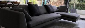 Modern corner sofa upholstered with dark fabric