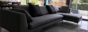 Gray corner sofa upholstered with fabric