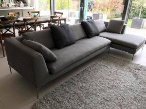 Modern corner sofa upholstered with gray fabric