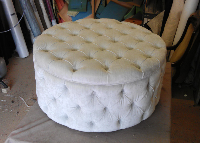 Round pouf upholstered with soft fabric