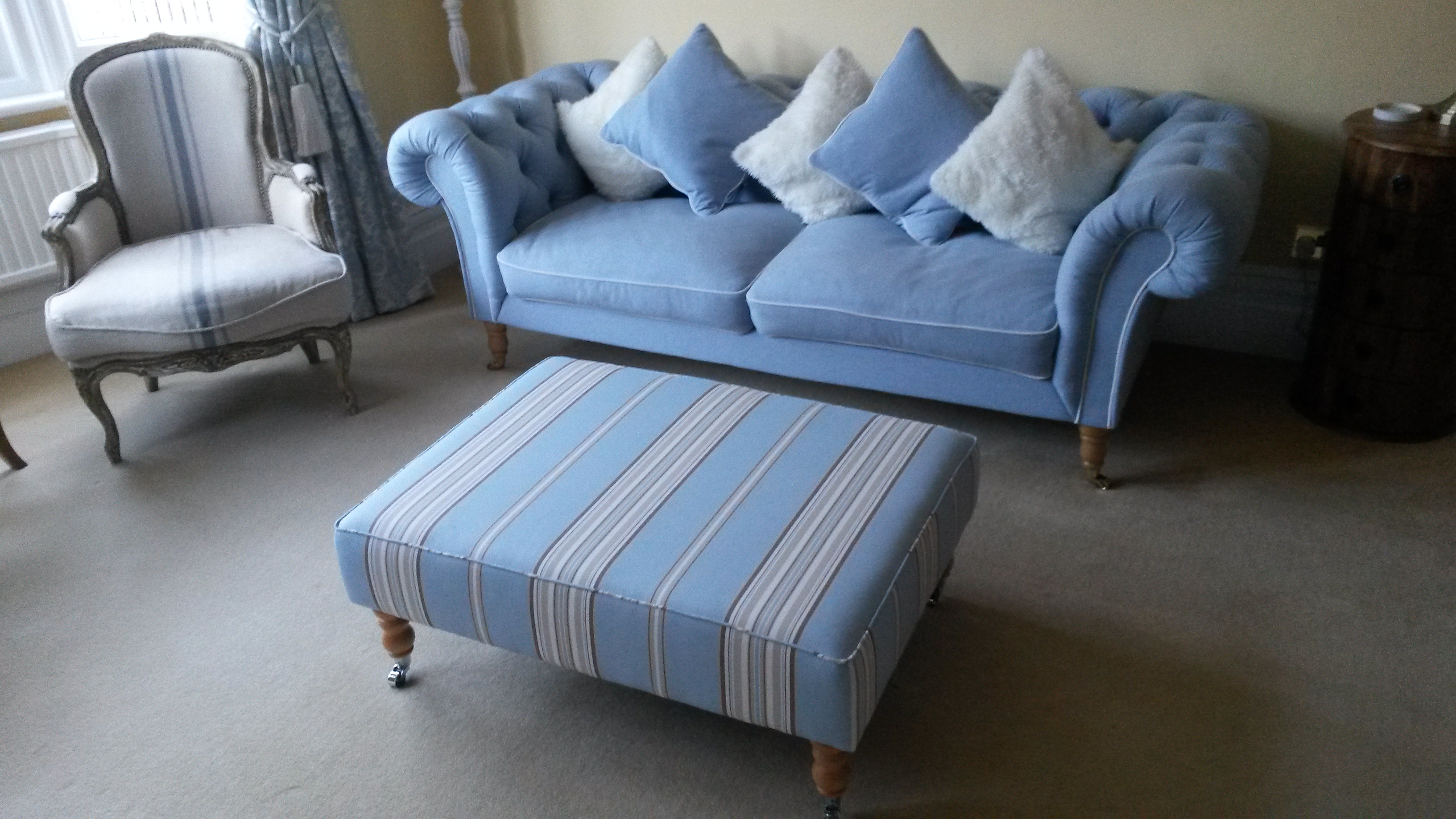 Sofa with cusions and footrest upholstered with light blue fabric