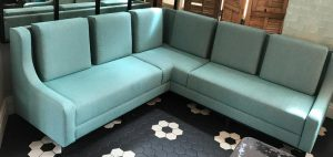Modern corner sofa upholstered with light green fabric