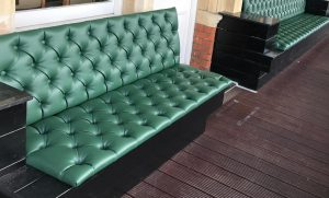 Pub seat upholstered with green leather